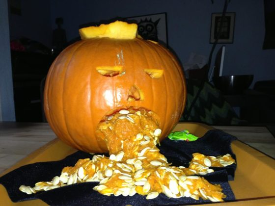 Photo of a Halloween jack-o-lantern with pumpkin seeds coming out of its mouth, looking like vomit
