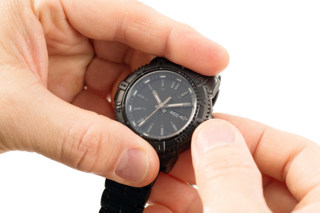 Photo of hands setting time on watch