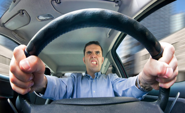 Photo of angry man gripping vehicular steering wheel