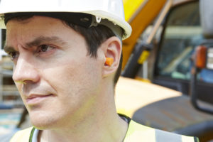 Photo of construction worker in hard hat wearing hearing protection (ear plugs)