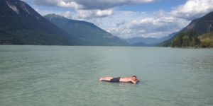 Photo of a person lying on an air mattress floating on a lake