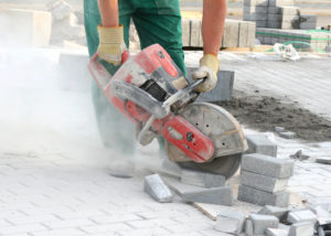 Photo of construction worker using saw to cut concrete and producing silica dust