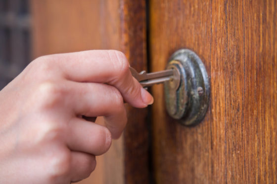 Photo of a hand holding a key, unlocking a door