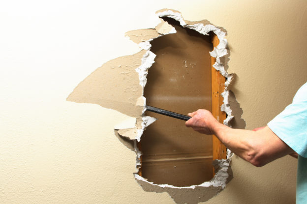 Photo of person with crowbar in hand removing drywall