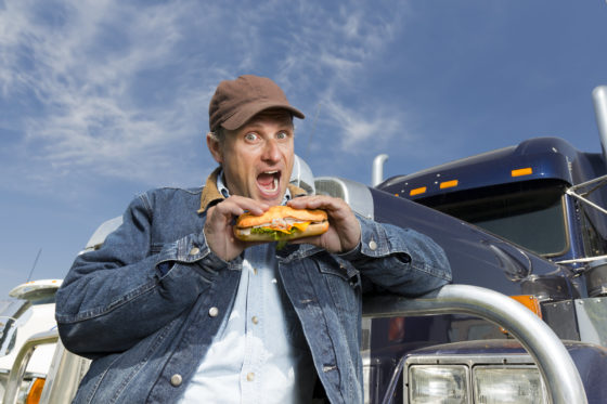 Photo of truck driver eating loaded sub sandwich in front of truck.