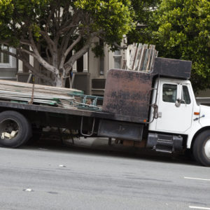Photo of a flatbed truck delivering metal scaffolding, parked on a downhill slope
