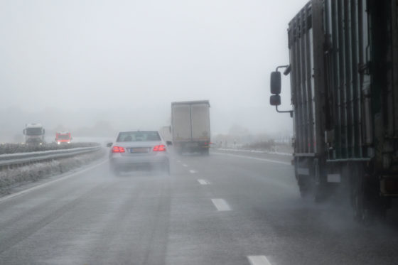Photo of car and trucks driving on highway in winter