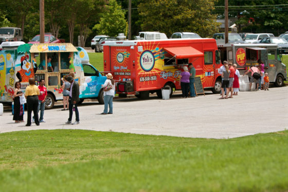 Photo of colourful food trucks with people lined up