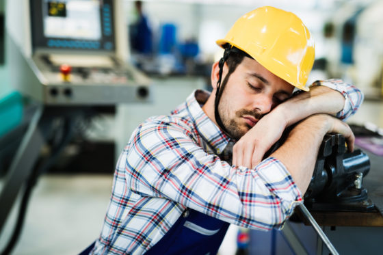 Photo of worker in hardhat sleeping on the job