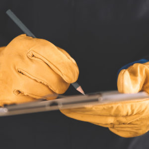 Photo of hands in work gloves, making notes on a clipboard