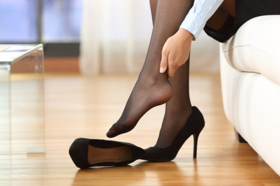 Photo of woman with tired, painful feet from wearing high heels