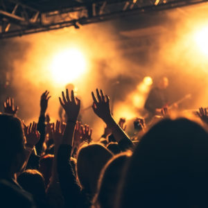 Photo of crowd waving at stage at live concert