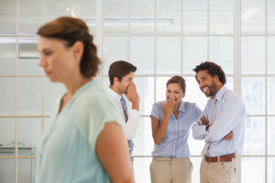 Photo of unhappy woman whose co-workers are talking about her