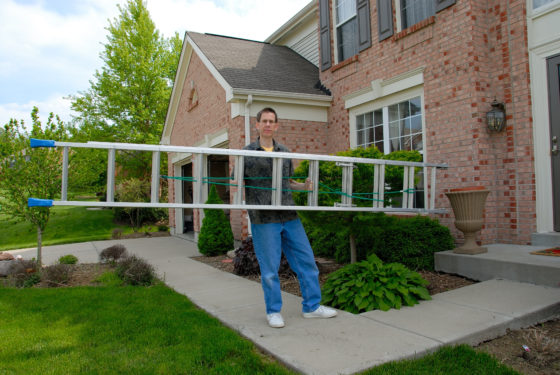 Photo of man carrying extension ladder in front of house