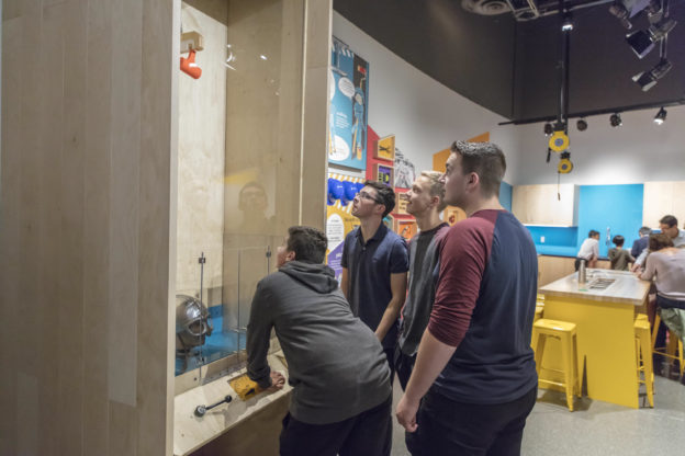 Photo of youths at a science exhibit where a hammer smashes safety helmets