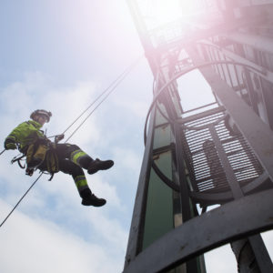 Photo of worker in safety gear abseiling down from a tower