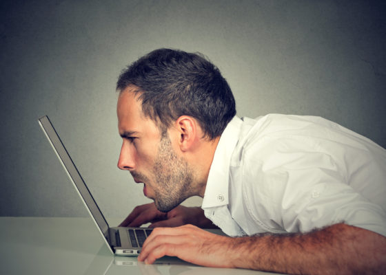 Photo of man with vision problems with his face almost touching laptop screen