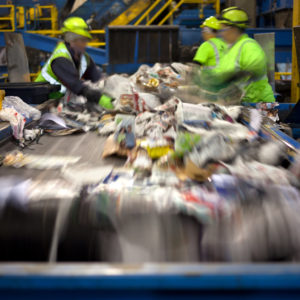 Photo of workers at a conveyor sorting materials for recycling