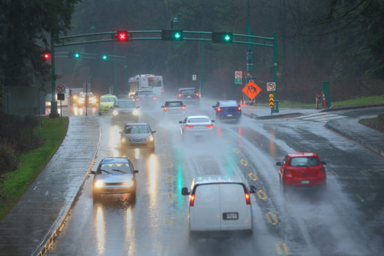 Photo of busy multi-lane roadway with signs and lights, and heavy rain