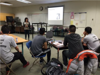 """Robin Schooley of ILS Young Worker team delivering a presentation to the WorkSafeBC Youth Leadership Team from Richmond high schools. Students are wearing their """"Live for Tomorrow"""" t-shirts."""