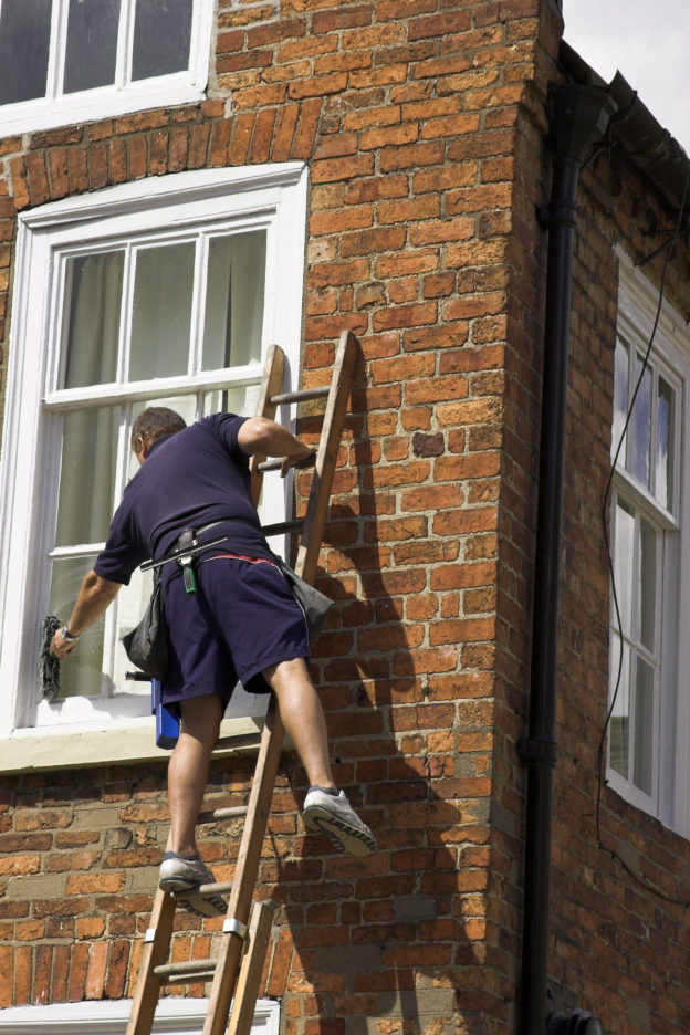 Photo of man leaning sideways off a ladder to wash a window