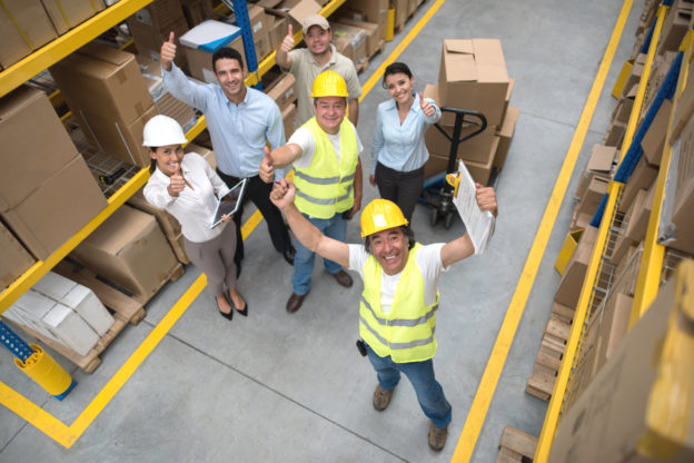 Photo of workers in warehouse giving the thumbs up signal