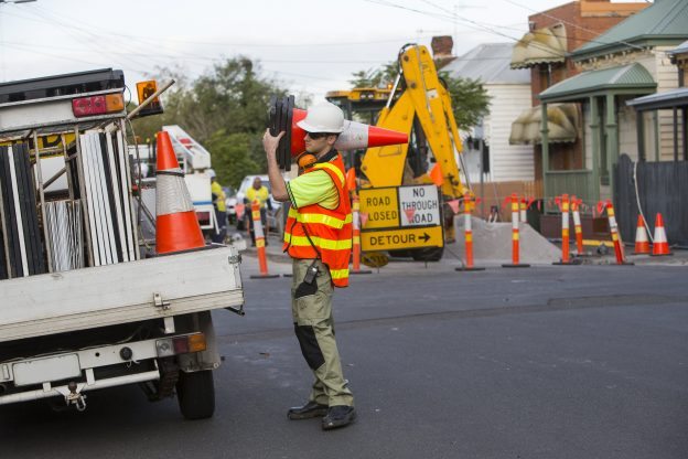 Photo of worker in high-vis PPE carring traffic cones