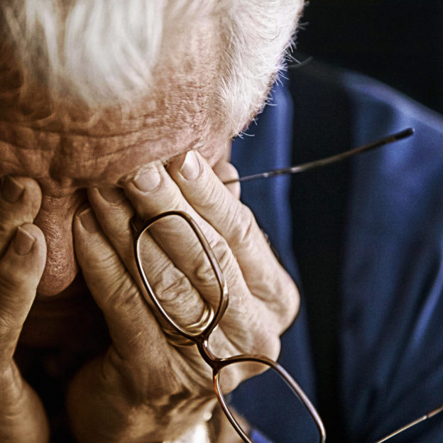 Photo of older man with head in his hands