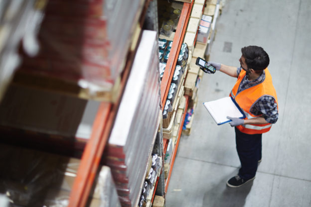 Photo of worker checking barcodes of stock in warehouse racking