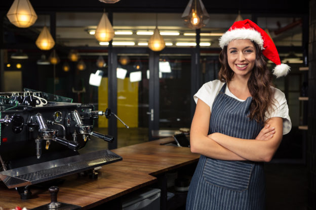 Photo of a barista wearing a santa hat and standing beside a coffee machine