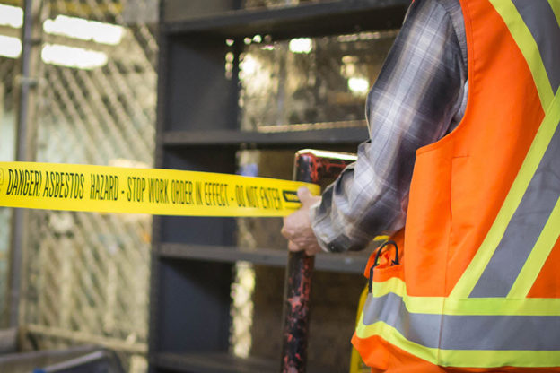 Photo of worker in high-vis vest in front of hazard tape