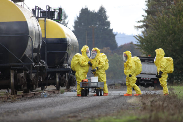 Photo of HAZMAT team beside tanker railcars
