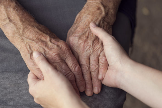 Photo of an older person's hands held caringly in a younger person's hands