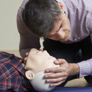 Photo of a man in a first aid class checking airway of CPR dummy