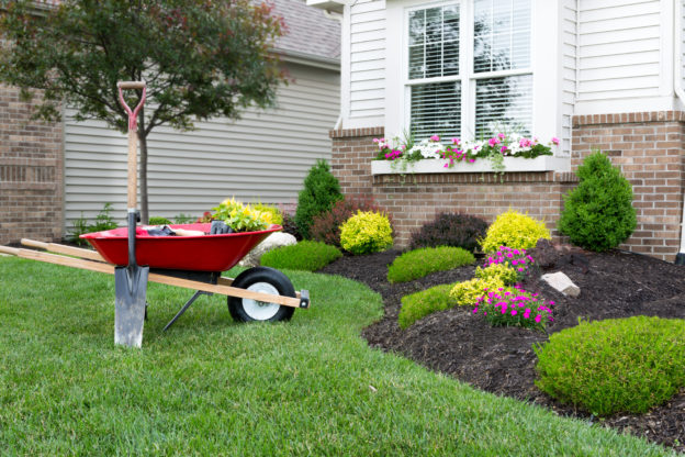 Photo of a wheelbarrow and shovel next to a flowerbed outside a home