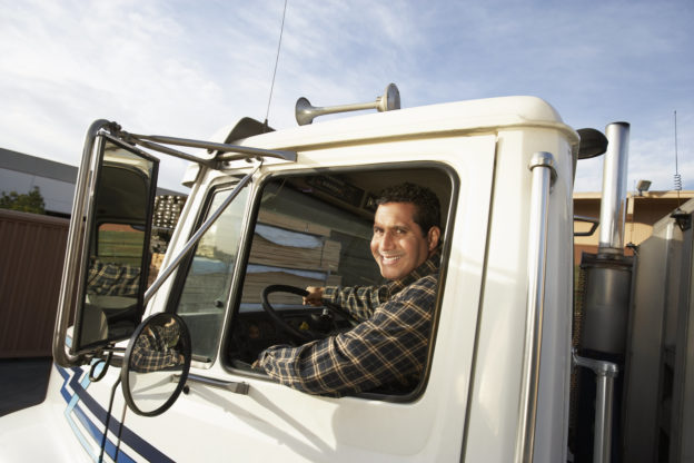 Photo of smiling truck driver in cab of semi truck