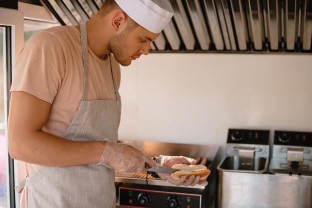 Photo of a cook in a food truck preparing a hotdog bun