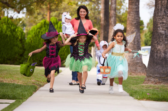 Photo of woman taking children in Halloween costumes along a sidewalk