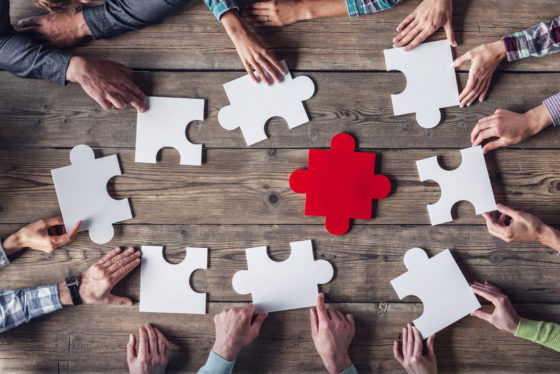 Photo of multiple hands holding large puzzle pieces, around a table