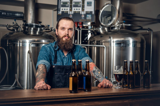 Photo of tatooed man behind counter in a craft brewery