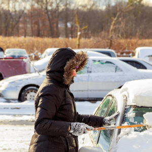 Photo of woam in dark hooded coat and mitts clearing snow from car windows