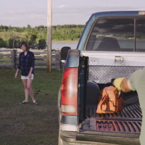 Photo of rancher putting tools in pickup truck with family in background