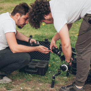 Photo of two young men changing lenses on a camera
