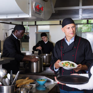Photo of chef and staff in kitchen of restaurant