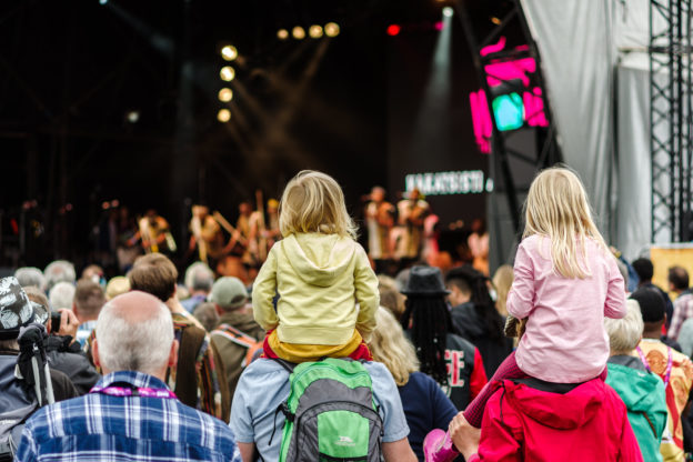 Photo of children on shoulders of adults in audience of concert on big stage