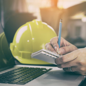 Photo of laptop, notebook, hands with pencil, and hard hat