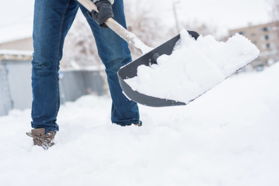 Photo of person in jeans in deep snow with a shovel full of snow