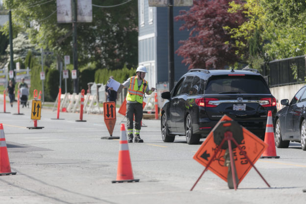 Photo of traffic control person speaking to driver of black SUV, amid traffic cones and signs