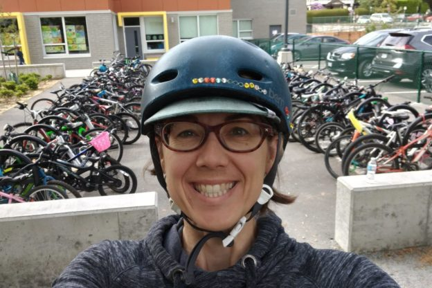 Photo of Lisa Corriveau wearing bike helmet, in front of rows of bikes at her kids' school