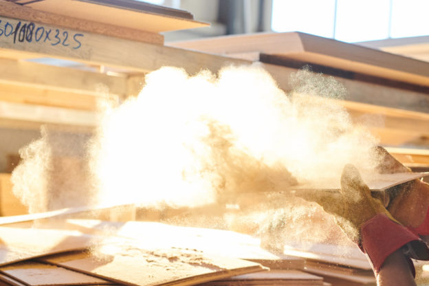 Photo of sawdust being blown off a board in a wood products plant